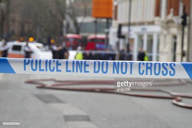 police line do not cross tape against blurred city background - cordon tape stock pictures, royalty-free photos & images