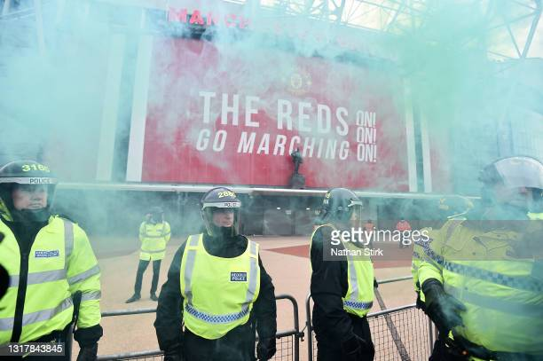 Police line is seen as fans set of smoke flares as they protest at Old Trafford on May 13, 2021 in Manchester, England. Police and ground security...