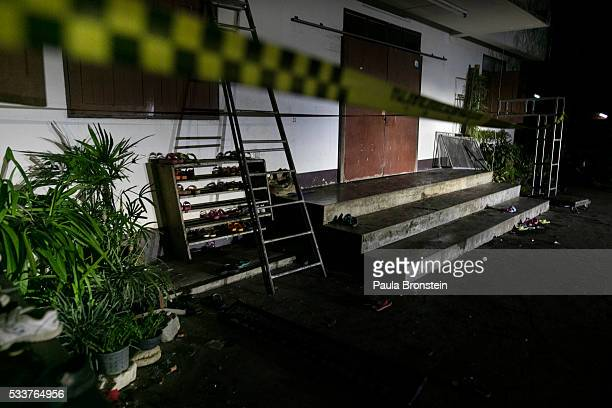 A police line is seen outside of the school dormitory where a fire broke out on Sunday night killing at least 17 girls in Wiang Papao Chiang Rai...