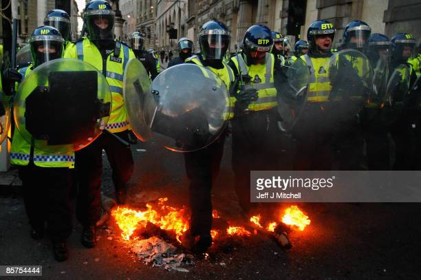 A police line marches through a fire started by protesters as they try to stop anti capitalist and climate change activists demonstrating in the City...