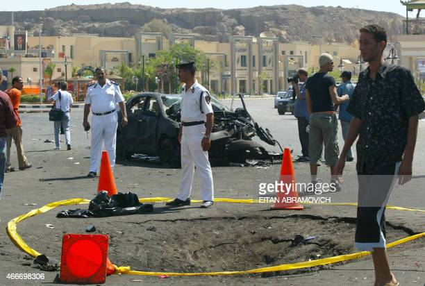 A police line secures the crater left by a car bomb detonated in front of a shopping mall 24 July 2005 in the Red Sea resort of Sharm elSheikh 500...
