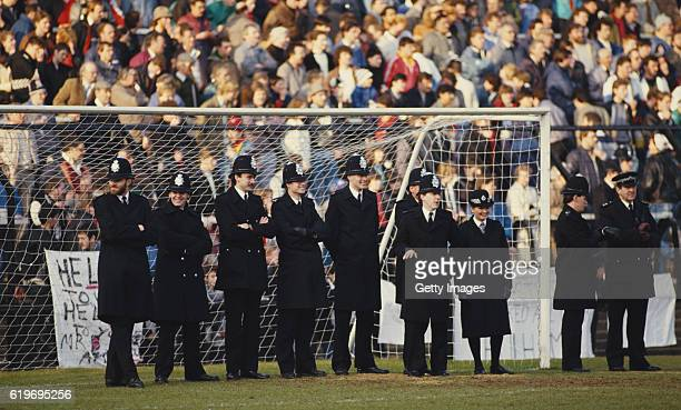 Police line the goalmouth as Fulham fans protest at a possible merger with Queens Park Rangers during their match against Walsall at Craven Cottage...