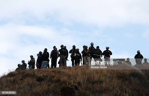 Police line the hill and spray water to wet the path up towards them as protesters gather below on Turtle Island at Standing Rock on Nov. 24 during...