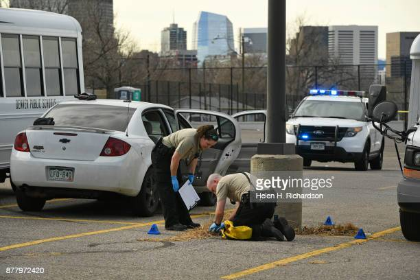 DENVER CO NOVEMBER 23 Police look for shells from a gun as they investigate the scene of an early afternoon shooting in the parking lot of Manual...
