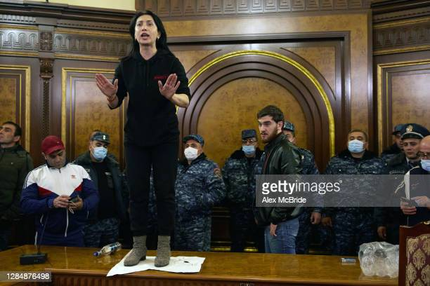 Police look on as a woman shouts among protestors who have stormed Armenian Prime Minister, Nikol Pashinian's office after the announcement of a...