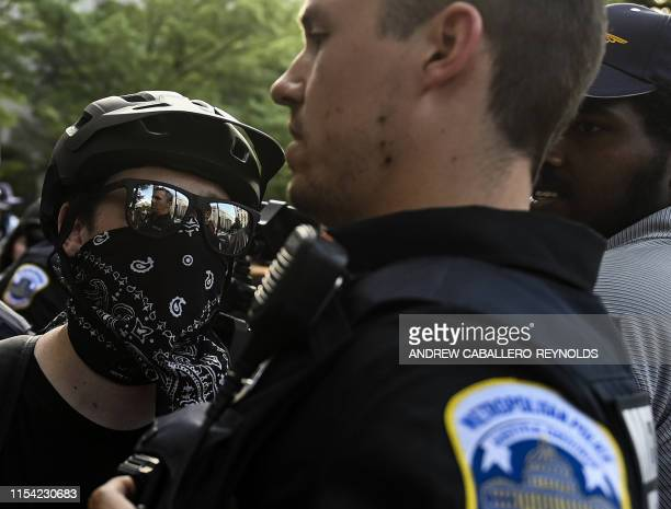 Police look on as an antifascist or Antifa member confronts them in front of the Trump Hotel after a far right Demand Free Speech rally in Washington...