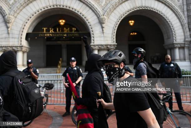 Police look on as antifascist or Antifa members walk past the Trump Hotel after a far right Demand Free Speech rally in Washington DC on July 6 2019
