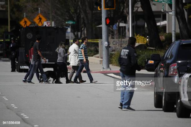 Police look on as employees walk across the streer outside of the YouTube headquarters on April 3 2018 in San Bruno California A woman opened fire at...