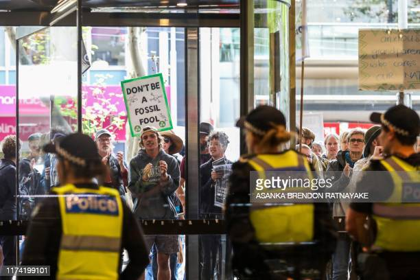 Police look on as protesters gather outside the office building of Energy Australia to mark the beginning of the Extinction Rebellion protests in...