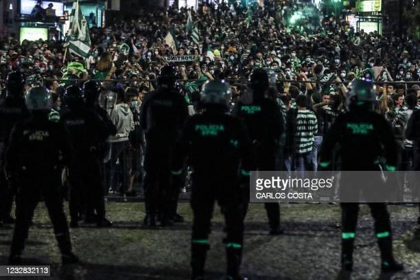 Police look on as Sporting fans celebrate inside a safety box after Sporting CP won the Portuguese football League title at Marques de Pombal in...