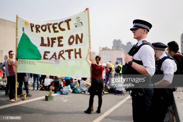 Police look on at climate change activists blockading Waterloo bridge on the third day of an environmental protest by the Extinction Rebellion group...