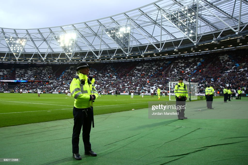 Police look on at the fans after the Premier League match between West Ham United and Burnley at London Stadium on March 10, 2018 in London, England.