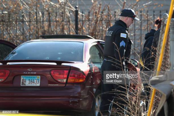 Police look over a bulletriddled car after a gunman opened fire killing a twoyearold child a man in his twenties and wounding a pregnant woman in the...