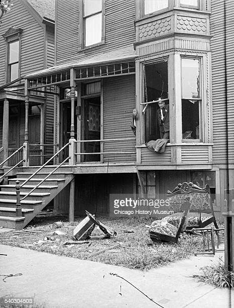 Police looking through a broken window of a house during the race riots in Chicago Illinois 1919 Broken furniture is strewn about the front yard