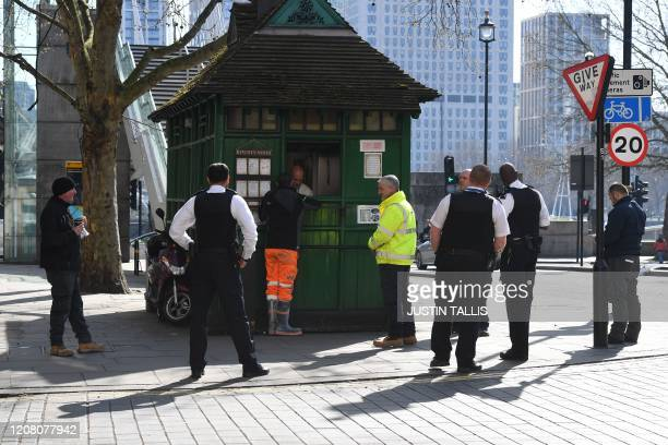 Police looks on as workers observe social distancing as they queue for food at a kiosk in central London on March 24 2020 after Britain ordered a...