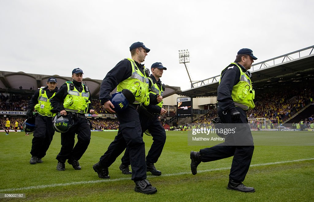 Police make their way off the pitch at Vicarage Road stadium