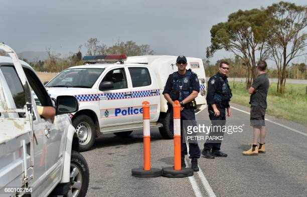 Police man a road block at floodwaters near the Queensland town of Bowen on March 29 after the area was hit by Cyclone Debbie Towns remained cut off...