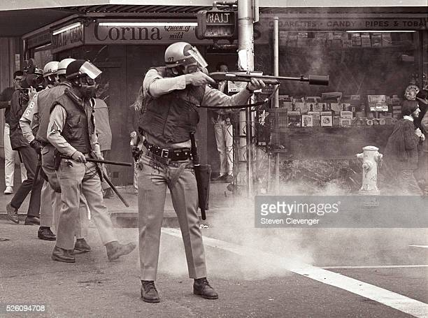 Police man fires a tear gas canister at rioters during an anti-war protest, turned riot, near the UC Berkeley campus. The canister is attached to the...