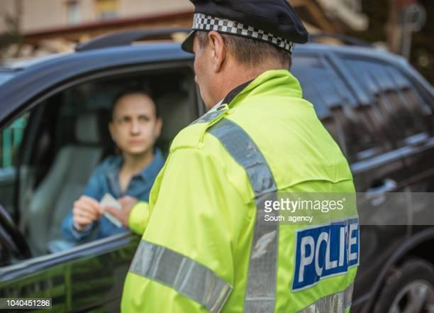 polizist einen strafzettel geben - bestrafung stock-fotos und bilder