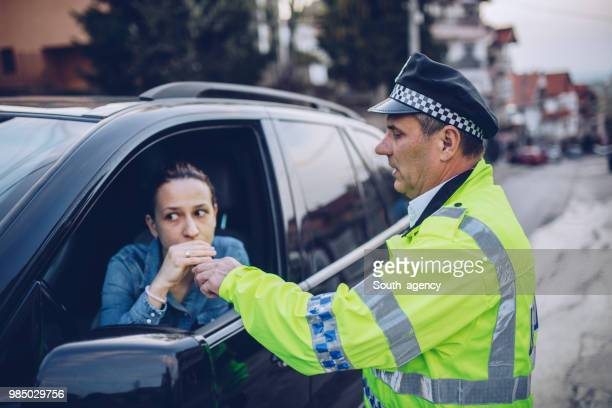 police man giving woman an alcohol test - south_agency stock pictures, royalty-free photos & images