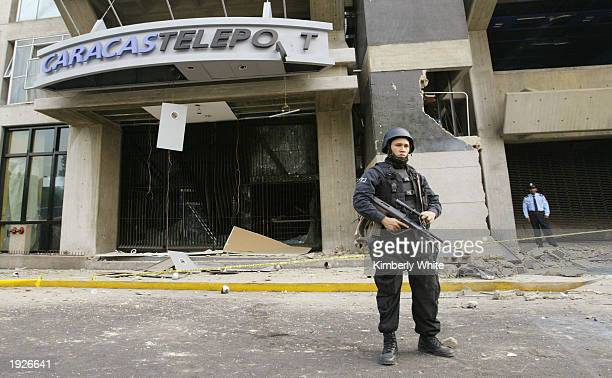 A police man guards a building where a bomb exploded April 12 2003 in Caracas Venezuela A bomb ripped through a building where government and...