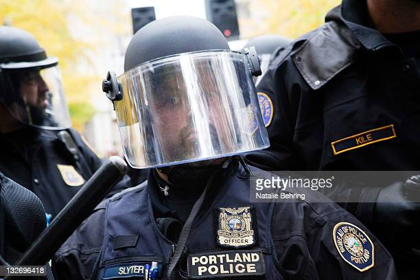 A police man in riot gear watches as protesters continue to chant slogans and sing songs near the Occupy Portland encampment November 13 2011 in...