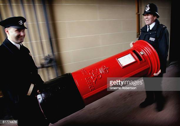 Police man laughs as he helps to carry a post box in to the quadrangle of Buckingham Palace as part of the 'Avenue of Design' a showcase of iconic...