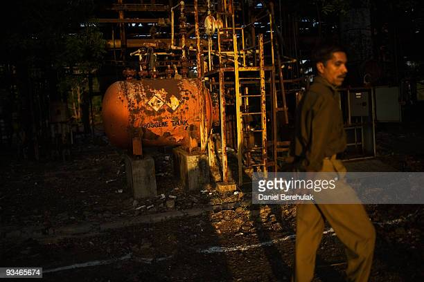 A police man looks on as he tours the site of the deserted Union Carbide factory on November 28 2009 in Bhopal India Twentyfive years after an...
