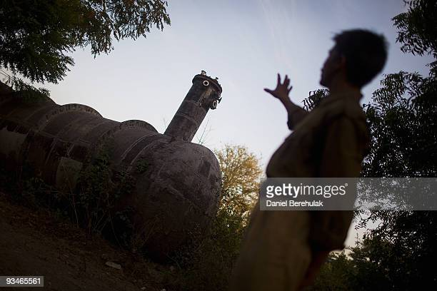 A police man points to the gas tank which leaked its contents into the atmosphere at the site of the deserted Union Carbide factory on November 28...