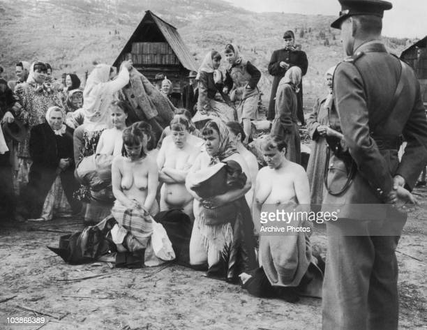 A police man stands by as Doukhobors disrobe in naked protest at some of their members who had became too 'worldly' British Columbia Canada circa...