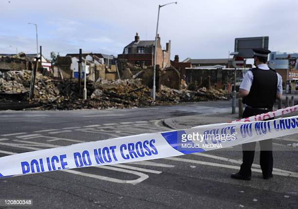 Police man the cordons beside the charred remains of Reeves furniture store in Croydon south of London on August 10 following riots in the area on...
