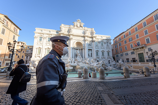 Police man wearing a face mask walks across the deserted Trevi Fountain square, Rome, Italy 1211543115
