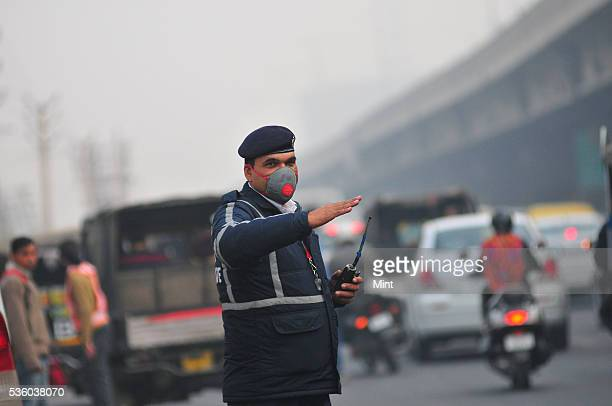 Police managing the traffic at a peak hour with masks to protect himself against pollution in the city on December 8 2015 in Gurgoan India