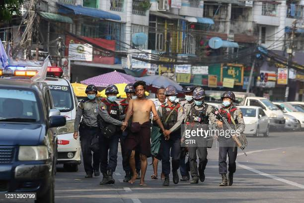 Police march with a resident arrested during a crackdown on protesters holding rallies against the military coup in Yangon on February 26, 2021.