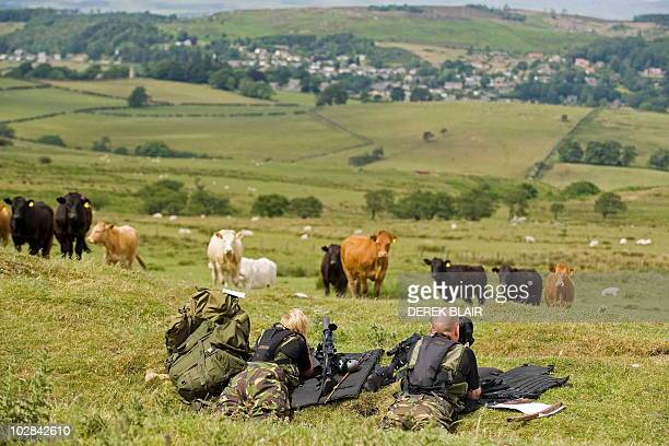 Police marksmen lie in the grass during their search for Raoul Moat, on the hills surrounding Rothbury, in northeast England on July 7, 2010. British...