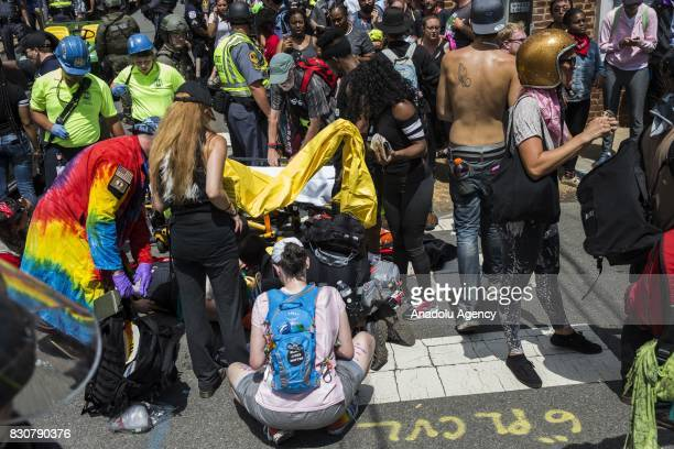 Police medical personnel and other protestors attend to the injured people after a car rammed into a crowd of antiWhite Supremacy protestors in...