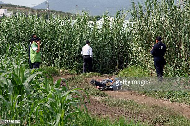 Police members and investigators stand next to the body of El Imparcial newspaper photojournalist Alberto Lopez Bello and another yet unidentified in...