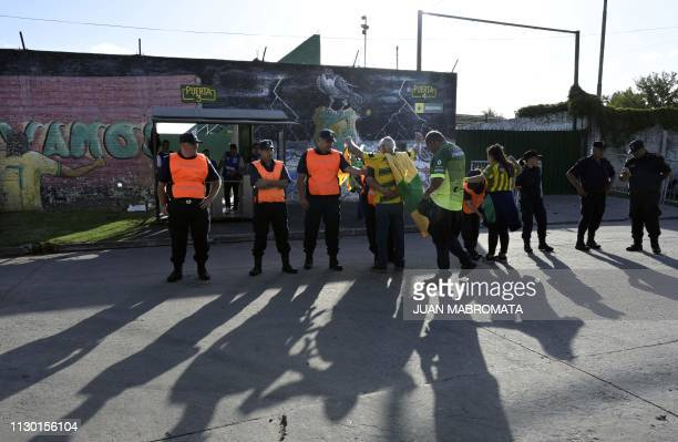 Police members frisk fans of Argentina's Defensa y Justicia upon arrival to attend Argentina's Superliga football match against Argentinos Juniors at...