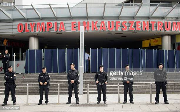 Police men guard the crime scene at OEZ shopping center the day after a shooting spree left nine victims dead on July 23 2016 in Munich Germany...