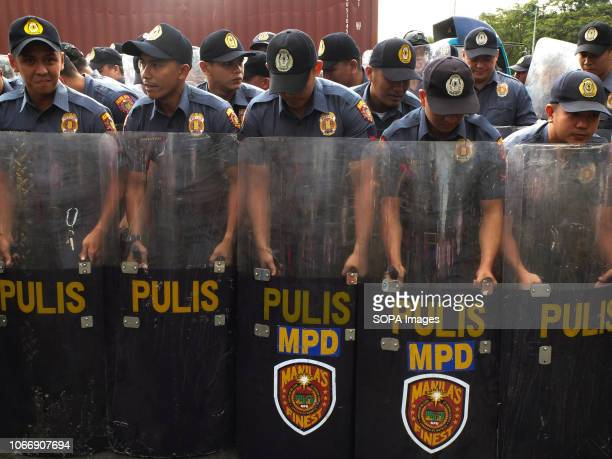 Police men of the Antiriot squad are seen holding firm their shields to block the protesters during the protest Leftist groups stage Bonifacio Day of...
