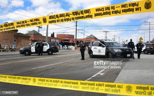 Police monitor a roadblock in front of the late Nipsey Hussle's The Marathon Store in Los Angeles California on April 2 2019 Grammynominated rapper...