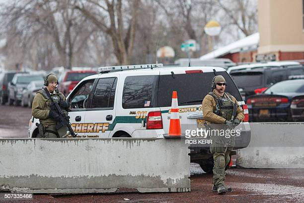 Police monitor a secure parking lot at the Harney County Courthouse in Burns Oregon on January 28 2016 A convoy of armoured vehicles rolled into a...