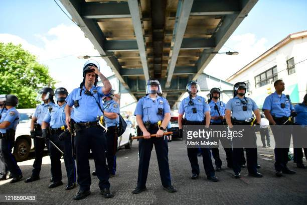Police monitor activity while forming a barrier during a protest of the death of George Floyd on May 31 2020 in Philadelphia Pennsylvania Protests...