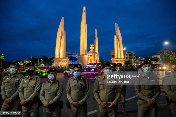 Police monitor antigovernment protesters as they take part in a Harry Potter themed rally in front of Democracy Monument on August 3 2020 in Bangkok...