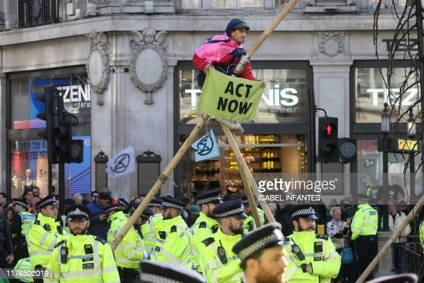 Police monitor as a climate activist perches on a makeshift structure in Oxford Street during the twelfth day of demonstrations by the climate change...