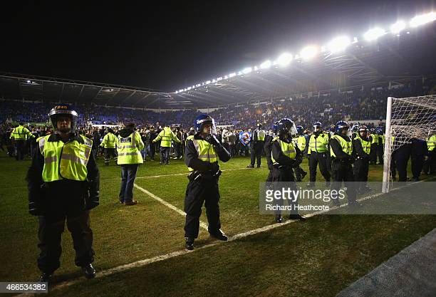 Police monitor fans as they invade the pitch after the FA Cup Quarter Final Replay match between Reading and Bradford City at Madejski Stadium on...