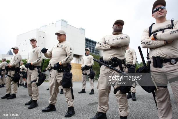 Police monitor the scene as demonstrators gather near the site of a planned speech by white nationalist Richard Spencer who popularized the term...