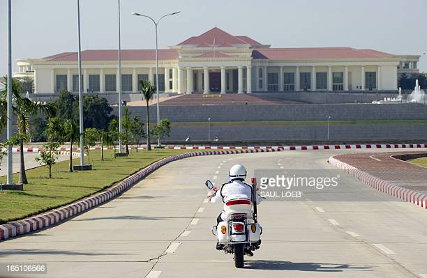 A police motorcycle approaches the President's Office prior to Myanmar President Thein Sein hosting US Secretary of State Hillary Clinton for a...