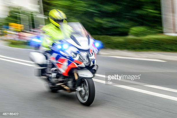 Police motorcycle cop driving by at high speed