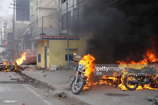 Police motorcycles burn after being set on fire during demonstrations against India's new citizenship law in Lucknow on December 19 2019 Indians...